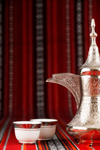 Arabian tea cups and a dallah are placed on traditional red fabric